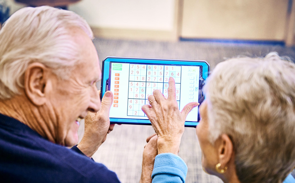 elders engaging with tablet playing sudoku in2l