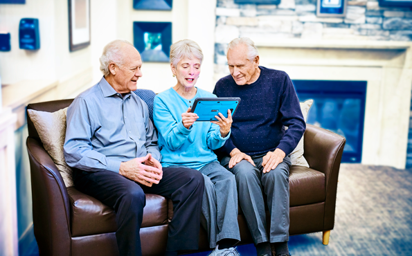 Three elders sharing tablet on couch